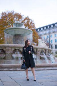 Dunkelblaues Spitzenkleid im Peplum-Schnitt kombiniert mit schwarzen Pumps, schwarzem Mantel mit Stickerei und einer Henkel-Handtasche: Fertig ist der Weihnachtslook für Heiligabend.