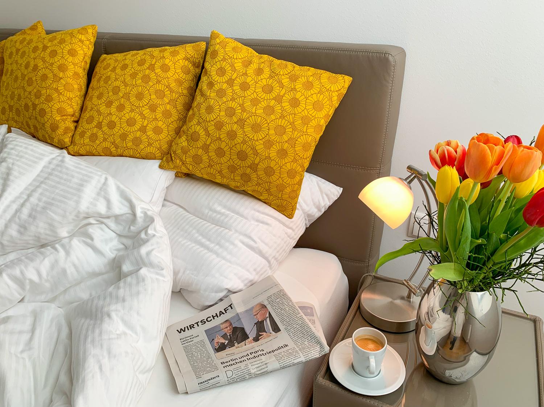 Kaffee und Zeitung im Bett im Schlafzimmer von Vienna Grand Apartments, einer Alternative zum Hotel in Wien