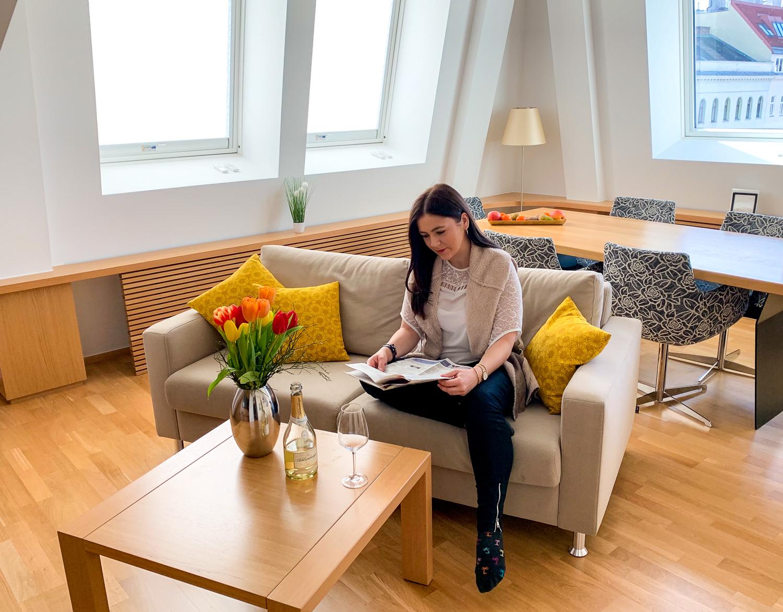 Zeitunglesen im Wohnzimmer in den Vienna Grand Apartments, einer Alternative zum Hotel in Wien