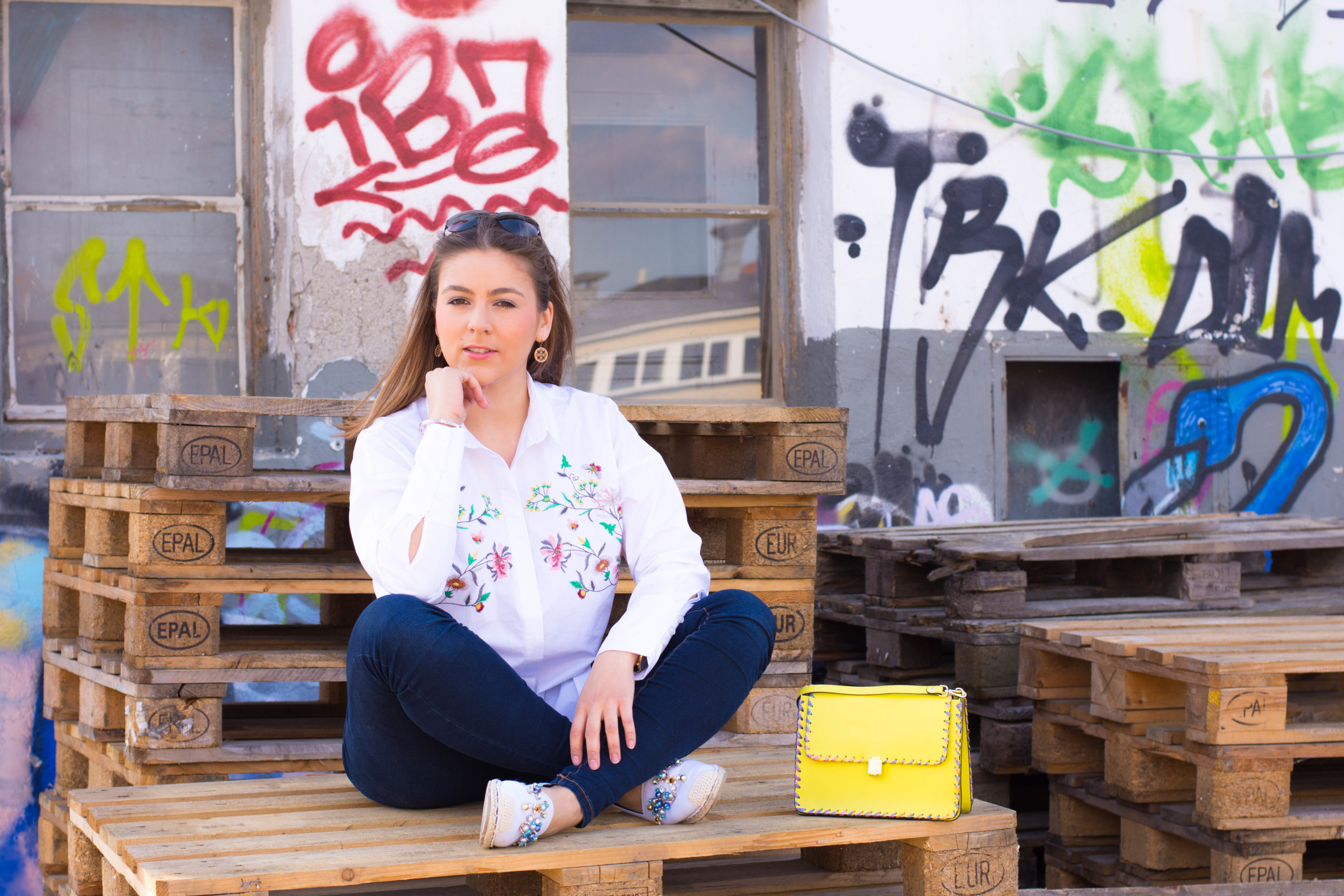 Im sommerlichen Alltagslook vor einer Graffitiwand